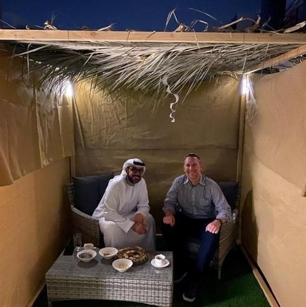 2 men sitting together in a Sukka